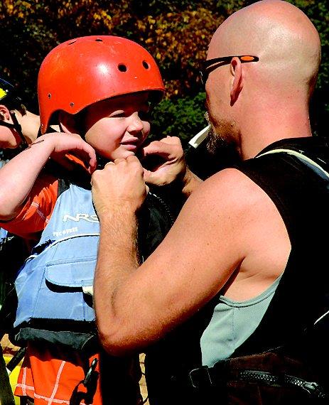 Dad Dan Kellogg adjusts one of his brood's helmet prior to entering the water.
